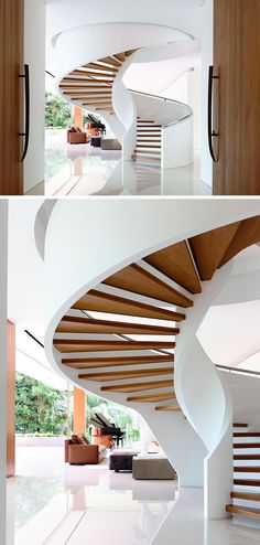 A grand spiral staircase created by floating wood treads between the two white sides rises up into the next floor and welcomes people as they enter the home.