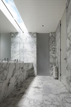 Marble tiling and marble benchtop it skylight at Docker Street Residence by B.E Architecture