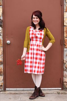 Red table cloth dress.  Contrasting mustard cardi.  White tight.  Brown boot.