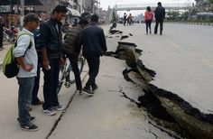 Nepalese residents walk past road damage following an earthquake in Kathmandu on April 26, 2015.