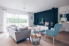 I like the one wall painted, it looks like, a dark teal. The pop of color from the blue chair and pillow