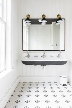 Black and white kids' bathroom features three gold and black industrial sconces lighting a black metal frame mirror hung from a white vertical shiplap wall above a black and white vintage trough sink.