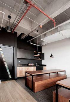 Minimalista, esta cozinha de tons sóbrios se aproveita do charme dos canos que, à mostra e unidos a luminárias, colorem o ambiente.