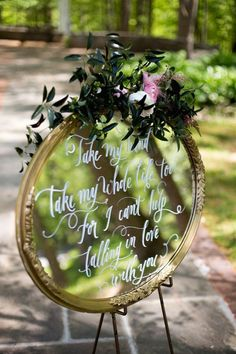 Go for a glam, fairy tale look by repurposing a vintage mirror with some beautiful calligraphy and florals.     Image via  Whimsical Wonderland Weddings.