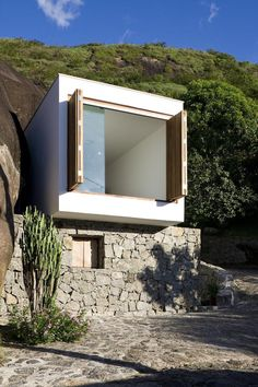 A small house in Brazil with traditional stone walls topped by a modern concrete box. It has 1 bedroom in 387 sq ft. | www.facebook.com/Smal...