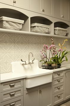Chic laundry room features coral pink cabinets paired with white