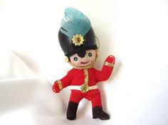 Vintage Christmas ornament, this flocked plastic toy soldier ornament has a blue feather on his hat. His boots and red are flocked and the white and gold trim are fabric. Hand painted face, gold stickers, gold hanging loop.  He is 3.75 inches (9.5 cm) tall.  Condition: Very good - a few thin spots in the flocking, hat paint is chipped in back.  Check here for more plastic ornaments: http://www.etsy.com/shop/bythewaysidexmas?section_id=15787776  Thanks for looking! I am happy to answer…