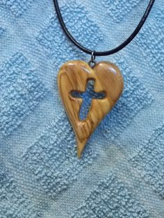 This is a hand-carved heart with a cross carved out within that I designed. This pendant is about 2 inches tall and comes on a black cord. To purchase please go to the Aguppywear sales page.