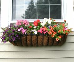 beau pot de fleur accroché au rebord de fenêtre
