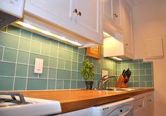 Glass tile backsplash helps reflect light in Newburyport condo remodel