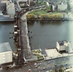 Die Stasi, von der dieses Foto stammt, hatte stets den Überblick. Im Gebäude links unten residiert heute die Plattenfirma Universal, im Gebäude rechts befindet sich eine Diskothek. Quer über die Straße hatte die DDR ein Abfertigungsgsgebäude eingerichtet, denn die Brücke war zum Grenzübergang geworden.
