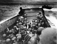 Allied troops crouch behind the bulwarks of a landing craft as it nears Omaha Beach.