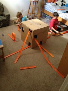 Cardboard box, exacto knife, a little duct tape, hotwheels tracks- tons of boy fun!