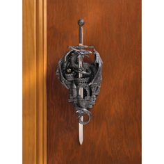 Dragon Castle Keep Dagger Decor Duo - The dramatic dagger and wall-mounted sheath in this Dragon Castle Keep Dagger Decor Duo features a battle weary castle and a fearsome dragon. This carefully detailed wall accent will bring about the age of medieval style in your home.