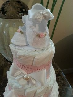 This listing is for one three tier light pink and white diaper cake. The cake stands 15 inches high (with baby shoes) and will arrive to you on its own beautiful cake plate.  Each cake tier is wrapped in beautiful pink chevron paper and white satin ribbon and finished with a pair of white baby shoes.   Cake Ingredients:  48 size 1 diapers 1 cake plate (not attached to cake) heaping spoon of pearls One pair of baby shoes (not attached to cake) Hand crafted embellishments  **********Help…