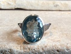 A great addition to our 2017 Collection! A large oval faceted aquamarine simply set in a flat sterling silver band. A perfect gift for March birthday girls or for anyone who loves a bit of sparkle!  (Model is wearing another of our aquamarine rings which is the same stone size.)   * Gemstone Size: approx. 14 X 11mm  * Ring Size: US 8. UK Size. Q  * Sterling Silver   This ring can be resized for a small charge. Please select Resizing option and enter size required in Notes section of order…