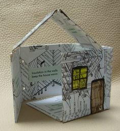 "House by Leslie Waygren. ""After I learned the wire-edge binding method, I played around with the geometric shapes I could make. I made a pyramid, then a box. Then I realized I could divide the top of the box in two to make a child's-drawing house. I covered the panels with pages from a building construction book. Then I painted it and added the child's-drawing windows and door. I wrote sentences about the parts of the house and put them on the appropriate panels of the building."""