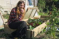 Leigh Bush tastes a spinach leaf growing inside her cold frame in Bloomington, Indiana.