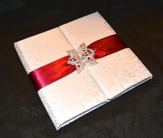 White gatefold folio wedding invitation with red ribbon and crystal buckle closure. Hand crafted by Lucky Invitations.