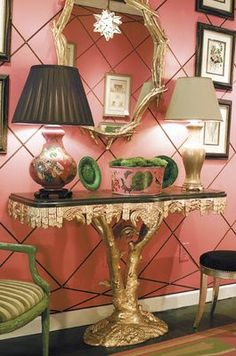 Chinoiserie foyer has a great pink on the walls, a palette of black, white, and gold, and then an accent color of green.