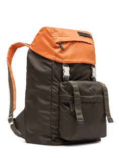 Backpack in nylon. Metal buckle fastening. 2 exterior zipped pockets with leather zipper pull. Contrasting colors. Adjustable shoulder straps.