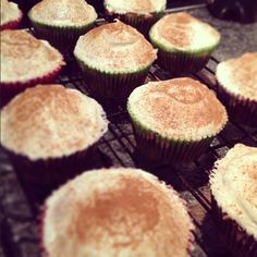 Carrot cake cupcakes with cream cheese icing and a sprinkling of cinnamon.