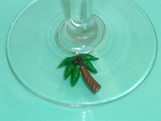 Palm tree polymer clay wine glass charm. For more information please visit www.CharmingSculptHers.com
