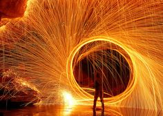 This image is a very clever design. It uses many props to create the photograph. It uses steel wool compacted and lit on fire and spun in a circular motion. The people in the photograph have to wear black clothes and protection.