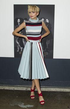 La celeb sceglie un look ladylike con un twist contemporaneo, vedi la gonna plissè in vernice a spicchi.  -cosmopolitan.it