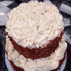 Close up of top-- piped 2d roses in cream cheese frosting, toasted coconut on sides