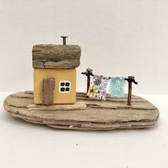 Little Yellow Wooden House, Miniature Seaside Cottage Ornament, Driftwood Art, Coastal Décor, Housewarming, New Home, Birthday, Christmas Gift A small seaside cottage ornament, hand made using driftwood sourced from Whitby in North Yorkshire, together with other reclaimed wood. The cottage is hand painted using yellow chalk paint and stands on a textured driftwood base. A small driftwood front door and tiny washing line add character to the scene. The roof is made from a section of…