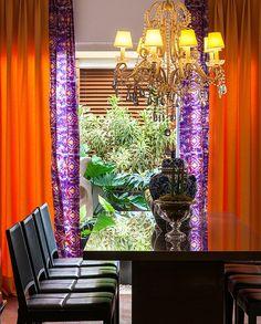 A sala de jantar tem vista para o jardim de inverno, o que deixa o espaço bem iluminado. A cortina laranja e roxa completa o ambiente (Foto: Divulgação/Romulo Fialdini). Projeto do designer de interiores Marcelo Arabe, publicado em Casa e Jardim.