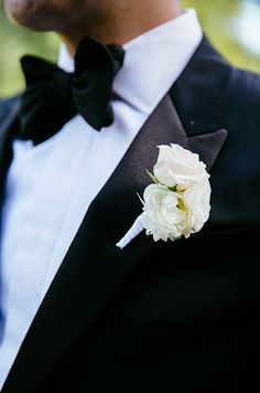 The groom's boutonniere is made of white ranunculus, roses and wrapped in white ribbon.