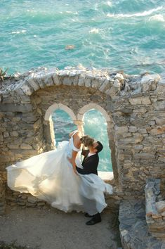 beautiful wedding photo by the sea ... Love the motion of her dress!