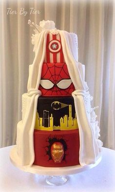 This husband insisted the white frosting curtain pulled back to reveal a superhero-themed tiered cake.