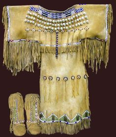 A superb Sioux fringed buckskin dress and moccasin outfit