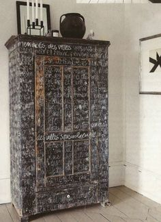 Chalkboard painted armoire with handwritten text. Nice texture and visual interest, dusty as hell.