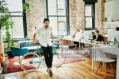 Stock Photo : Business owner leaning against bicycle in office