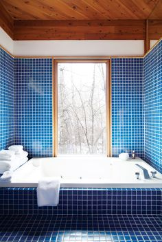 Blue tiled bathroom with wood ceiling and large bathtub