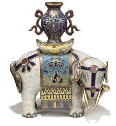A CHINESE CLOISONNE ENAMEL WHITE ELEPHANT  19TH CENTURY  Modelled standing foursquare with its head turned to the right, elaborately caparisonned and fitted with a saddle cloth enamelled with auspicious symbols, its back supporting a ribboned baluster vase. Christie's.