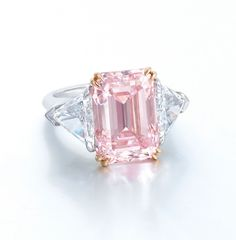 A SUPERB COLOURED DIAMOND AND DIAMOND RING  Set with a rectangular-shaped fancy intense pink diamond weighing approximately 9.07 carats, flanked by triangular-shaped diamonds, mounted in platinum and 18k rose gold, ring size 5¼