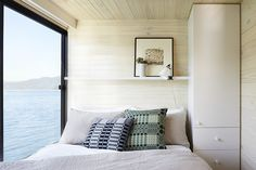 Neutral bedroom with light wood walls and a great view of the ocean // houseboat