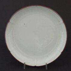 A 17th Century White Moulded Kakiemon Porcelain Dish of Nigoshide Body. The Center Moulded in Very Shallow Relief with Bamboo, the Six Border Panels moulded with Chrysanthemum. The Rim with a Brown Iron-Oxide Dressing.
