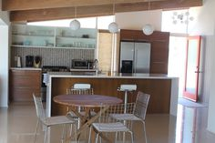 mid-century modern kitchen, warm wood, lights door, beams island's waterfall countertop