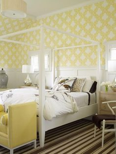 A lattice-patterned yellow wallpaper brightens this guest room, extending from crisp white wainscoting up to the crown molding. Chocolate-brown accents root the room in an earthy, natural scheme with wood finishes, a striped rug and botanical bedding. Design by Chris Sullivan Roughan; photography by Tria Giovan