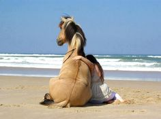 This is so cute! Girl and horse sitting down and enjoying the ocean breezes together.