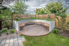 Circular deck with bench set within raised bed. Part of garden design in…