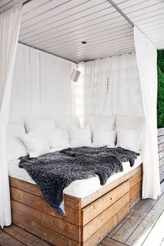 Create a romantic summer hideaway by styling an outdoor canopy bed with white drapery, a fluffy throw and ample cushioning for a relaxing outdoor space. #FieldNotes #OutdoorStyling #CanopyBed #Timber #Cushions