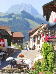 Gruyere Switzerland- medieval village with green rolling hills and snow capped mountains.