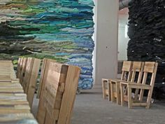 The dividing walls in the Haka building in Rotterdam are made of stacks of discarded clothes. It absorbs unwanted sound reflections and suits the interior design concept of using local reclaimed materials. The somewhat wobbly chairs are made of wooden slats.